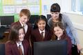 Elementary School Pupils With Teacher In Computer Class