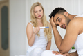 Young Couple Sitting In Bed, Woman Show Man Positive Pregnancy Test Conflict Relationships Problem
