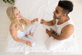 Young Couple Sitting In Bed, Smiling Woman Give Man Condom Lovers Contraception Protection