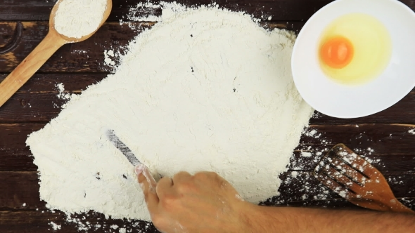 VideoHive Top View Young Man Writes a Word Food On White Flour At Wooden Desk From Above 18718253