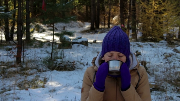 VideoHive Young Woman Drinking Hot Tea Or Coffee In Winter Forest 18727473