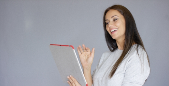 Download Happy Smiling Brunette Woman Video Chatting On Tablet Computer nulled download