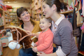 adorable girl look to toys at toy store with mother