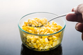 Spoonful of corn kernels with transparent bowl in reflective bac