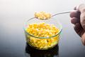 Selective focus on spoonful of corn kernels against dark backgro