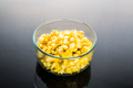 Corn kernels in transparent glass bowl in dark background