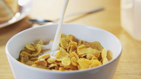 Bowl Of Cornflakes And Milk Pouring Milk In...