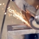 Worker With Angle Grinder Does Metalworking At Industrial Factory.
