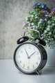 Old-time alarm clock on a white table with flowers