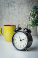 Old-time alarm clock on a white table with flowers and coffee cup