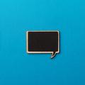 square empty chalk board speech bubble on blue paper