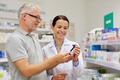 pharmacist showing drug to senior man at pharmacy