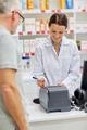 pharmacist writing check for customer at drugstore