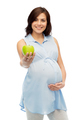 happy pregnant woman holding green apple