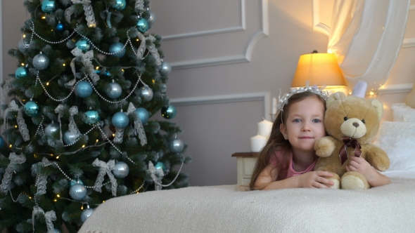 VideoHive Woman Lies On a Bed With a Teddy Bear Near a Christmas Tree 18769593