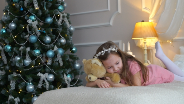 VideoHive Woman Lies On a Bed With a Teddy Bear Near a Christmas Tree 18769646