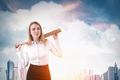 Businesswoman with baseball bat is standing in the city