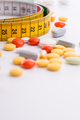 Pills and yellow measuring tape on the white table