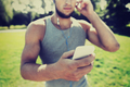 young man with earphones and smartphone at park