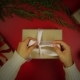 Hands Wrapping Christmas Presents On Red Background