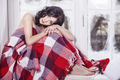 Beautiful woman sits at the winter window covered with a  blanke