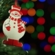 Christmas Background With Christmas Tree And Snowman On Background Of Blurred Lights