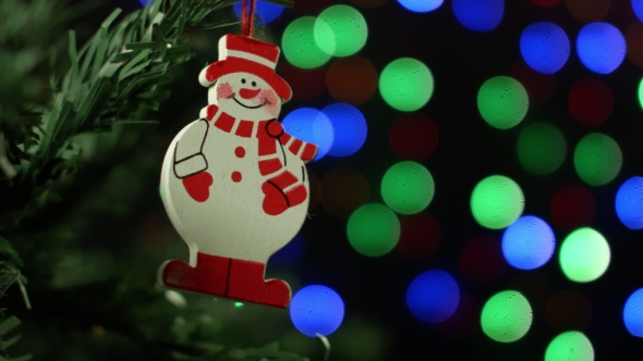 Christmas Background With Christmas Tree And Snowman On Background Of Blurred Lights Garlands