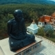 Aerial: Circling Around Monk Statue In Thai Temple.