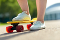 close up of female feet riding short skateboard