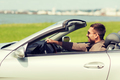 happy man driving cabriolet car outdoors