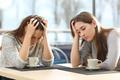 Two sad women in a coffee shop