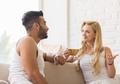Young Beautiful Couple Sit On Sofa Talking, Hispanic Man Woman Drink Morning Coffee Cup