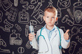 Little boy in doctor costume holding syringe and shows class on dark background with pattern.