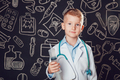 Happy little boy in doctor costume holding syringe on dark background with pattern.