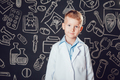 Little boy in doctor costume standing on dark background with pattern.