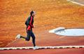 adult man running on athletics track