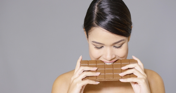 Download Pretty Woman Biting Into a Bar Of Chocolate nulled download