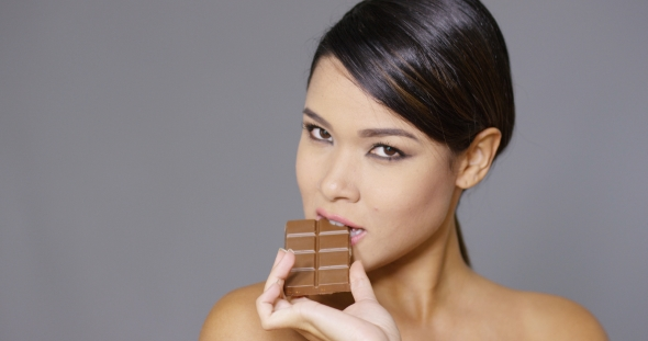 Download Sensual Young Woman Nibbling On a Chocolate Bar nulled download