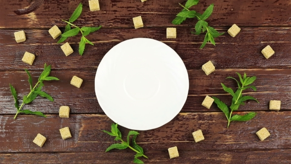 VideoHive A Man Puts a Cup of Tea on Table with Fresh Mint Leaves and Brown Sugar in Cubes on Brown Wooden 18880675