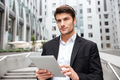 Pensive businessman using tablet in the city