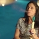 Attractive Girl Smoking Hookah Near the Pool with Blue Water Background.