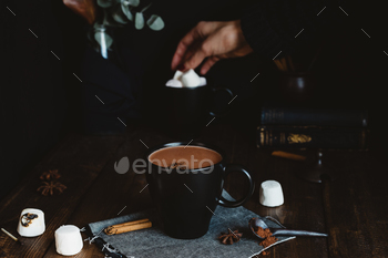 Comforting Mug of Hot Chocolate on Rustic Table with Female Hand Picking Marshmallows in Background