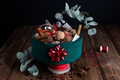 Horizontal View of Christmas Tin filled with Nuts and Spices on Rustic Table