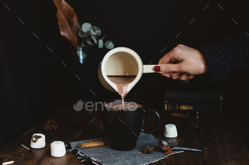 Female Pouring Hot Chocolate Drink from Milk Pan into Black Mug on Rustic Table