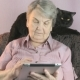 Elderly Woman Sits at Armchair Next To Black Cat