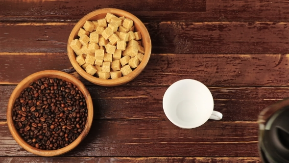 VideoHive Coffee Is Poured Into a White Cup on the Table on Him Located Brown Sugar Cubes and Roasted Coffee 18923907