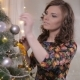 Beautiful Girl, Young Woman Decorating Christmas Tree, Put New Year Toys and Balls on Christmas Tree