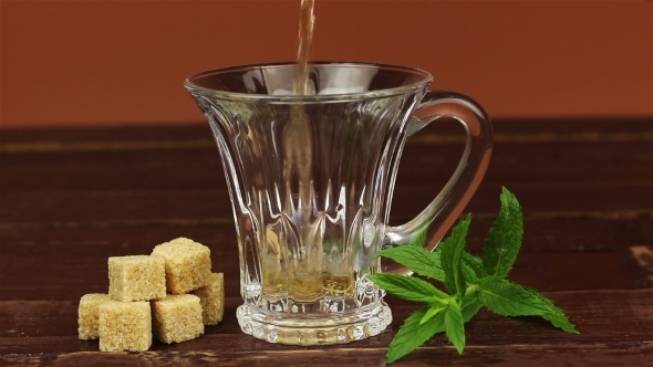 VideoHive Tea Being Poured Into Glass Tea Cup and Brown Sugar in Cubes with Mint Leaves on Brown Wooden Table 18939829