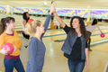 Women in bowling hall doing a high five