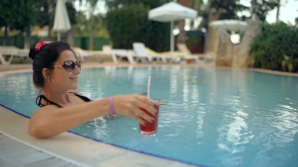 VideoHive Beautiful Lady Drinking a Cocktail in a Swimming Pool and Relaxing 18943133